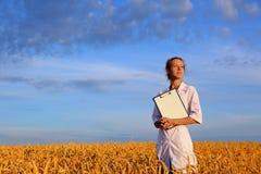 Agronom eller en student eller en forskare med dokumentet i hand i vetefältet arkivbild