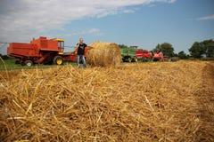Agronom i ett skördat fält med jordbruks- maskineri Arkivfoto