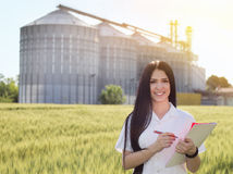Agronomist in field with silos behind Stock Photos