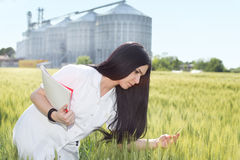 Agronomist in field with silos behind Stock Images
