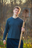 Agronomist handsome strong man with shovel on  background of flo Stock Image