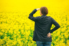 Agronomist standing in field of blooming cultivated rapese. Woman agronomist standing in the field of blooming cultivated rapeseed plantation, female royalty free stock images