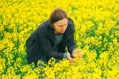 Agronomist woman examining oilseed rape flower blooming Royalty Free Stock Photography