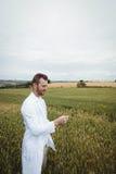 Agronomo che controlla i raccolti nel campo Fotografia Stock
