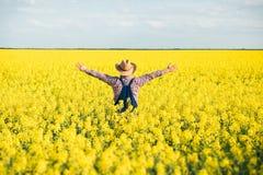 Agronomo che sta nel campo del seme di ravizzone coltivato di fioritura Immagine Stock