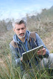 Agronomy scientist making research using tablet outdoors Stock Image