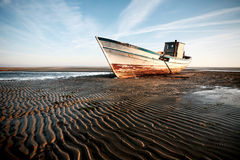 Aground boat on the beach. In the evening royalty free stock photos