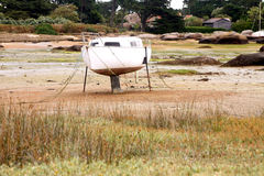 Aground boat. Aground white sailboat by low tide sea in Brittany royalty free stock images