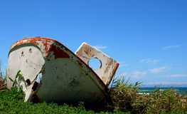 Aground life boat. Front view of an old aground life boat in the bushes before the sea in front of blue sky background royalty free stock photos