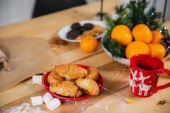 Agrume, caramelle gommosa e molle e croissant con gli attributi del nuovo anno sulla superficie di una tavola di legno fotografie stock