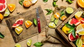 Agrumes coupés en tranches - pamplemousse, orange, mandarine, citron, chaux sur le vieux conseil avec la boîte Photo stock