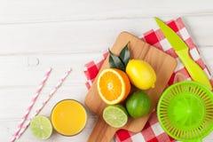 Agrumes et verre de jus Oranges, chaux et citrons Image stock