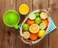 Agrumes et verre de jus Oranges, chaux et citrons Images stock