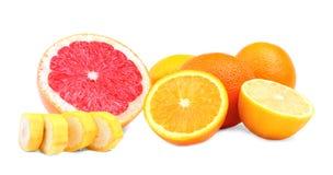 Agrumes organiques sur un fond blanc Une série de fruits tropicaux Pamplemousses, oranges, banane et un citron Photo libre de droits