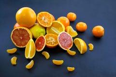 Agrumi colorati su un fondo blu scuro Fette di agrume e di buccia Citrus reticulata Citrus paradisi Citrus limon Fotografia Stock Libera da Diritti
