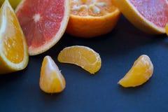 Agrumi colorati su un fondo blu scuro Fette di agrume e di buccia Citrus reticulata Citrus paradisi Citrus limon Fotografie Stock