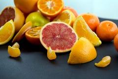 Agrumi colorati su un fondo blu scuro Fette di agrume e di buccia Citrus reticulata Citrus paradisi Citrus limon Immagini Stock