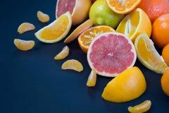 Agrumi colorati su un fondo blu scuro Fette di agrume e di buccia Citrus reticulata Citrus paradisi Citrus limon Immagine Stock