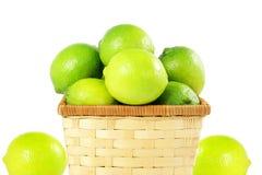 Agrumi freschi della calce del limone in canestro di bambù nel fondo bianco Fotografia Stock
