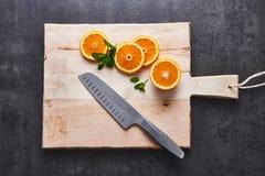 Agrumi freschi, fette arancio del mezzo taglio sul tagliere con il coltello su fondo di pietra scuro, disposizione piana fotografia stock