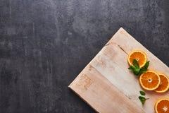 Agrumi freschi, fette arancio del mezzo taglio sul tagliere, fondo di pietra scuro, disposizione piana immagine stock libera da diritti