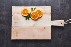 Agrumi freschi, fette arancio del mezzo taglio sul tagliere, fondo di pietra scuro, disposizione piana fotografie stock