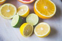 Agrumi pompelmo, arancia, limone, calce, sui precedenti di legno immagini stock
