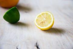 Agrumi pompelmo, arancia, limone, calce, sui precedenti di legno immagine stock libera da diritti