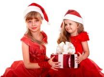 Agrupe al niño en el sombrero de Papá Noel con el rectángulo de regalo rojo. Imagen de archivo libre de regalías