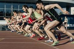 Agrupe atletas dos homens do começo em uma distância dos batalhadores de 1500 medidores no estádio Fotografia de Stock Royalty Free