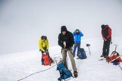 Agrupe a caminhada da cimeira de Hvannadalshnukur da geleira no parque de Vatnajokull da paisagem da montanha de Islândia nevoent Fotos de Stock Royalty Free