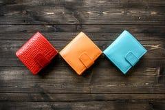 Agrupe a carteira colorida da pele de couro no fundo de madeira Foto de Stock Royalty Free