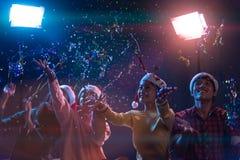Agrupe a dança nova asiática dos amigos regada com o togethe dos confetes Imagem de Stock
