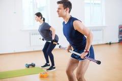Agrupe el calentamiento de la gente, haciendo entrenamiento del ejercicio del poder en club de fitness imagen de archivo