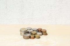 Agrupe el dinero de la moneda del baht tailandés en la madera contrachapada y el muro de cemento Fotografía de archivo