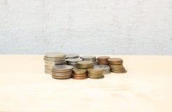 Agrupe el dinero de la moneda del baht tailandés en la madera contrachapada y el muro de cemento Foto de archivo