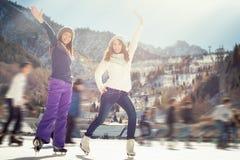 Agrupe el patinaje de hielo divertido de las muchachas de los adolescentes al aire libre en la pista de hielo Imagen de archivo libre de regalías
