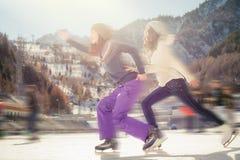 Agrupe el patinaje de hielo divertido de los adolescentes al aire libre en la pista de hielo Imágenes de archivo libres de regalías
