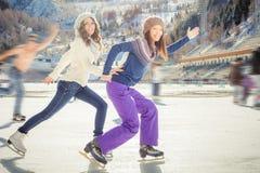 Agrupe el patinaje de hielo divertido de los adolescentes al aire libre en la pista de hielo Foto de archivo