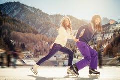 Agrupe el patinaje de hielo divertido de los adolescentes al aire libre en la pista de hielo Fotografía de archivo libre de regalías