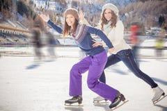 Agrupe el patinaje de hielo divertido de los adolescentes al aire libre en la pista de hielo Fotos de archivo libres de regalías