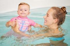 Agrupe el retrato de la hija caucásica blanca de la madre y del bebé que juega en el salto del agua en piscina dentro, mirando in foto de archivo
