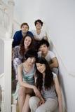 Agrupe el retrato de los amigos jovenes que se sientan en escalera Foto de archivo libre de regalías