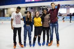 Agrupe el tiro de amigos adolescentes en la pista de patinaje de hielo de la pista Imágenes de archivo libres de regalías