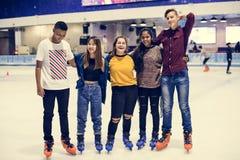 Agrupe el tiro de amigos adolescentes en la pista de patinaje de hielo de la pista Imagen de archivo libre de regalías