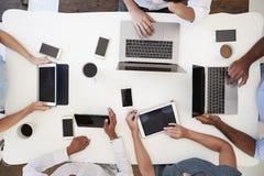 Agrupe el trabajo en los ordenadores con los teléfonos, tiro de arriba foto de archivo libre de regalías
