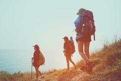 Agrupe jovens mulheres dos caminhantes que andam com trouxa em uma montanha no por do sol foto de stock