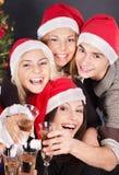 Agrupe a la gente joven en el sombrero de santa en el club nocturno. Imagen de archivo libre de regalías