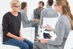 Agrupe la sesión de terapia con el terapeuta y el cliente en primero plano Fotografía de archivo libre de regalías