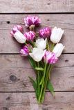 Agrupe las flores violetas del od y blancas brillantes de los tulipanes en de madera envejecida Fotografía de archivo
